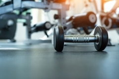 The dumbbell put on ground floor,at fitness room,warm light tone,blurry light around