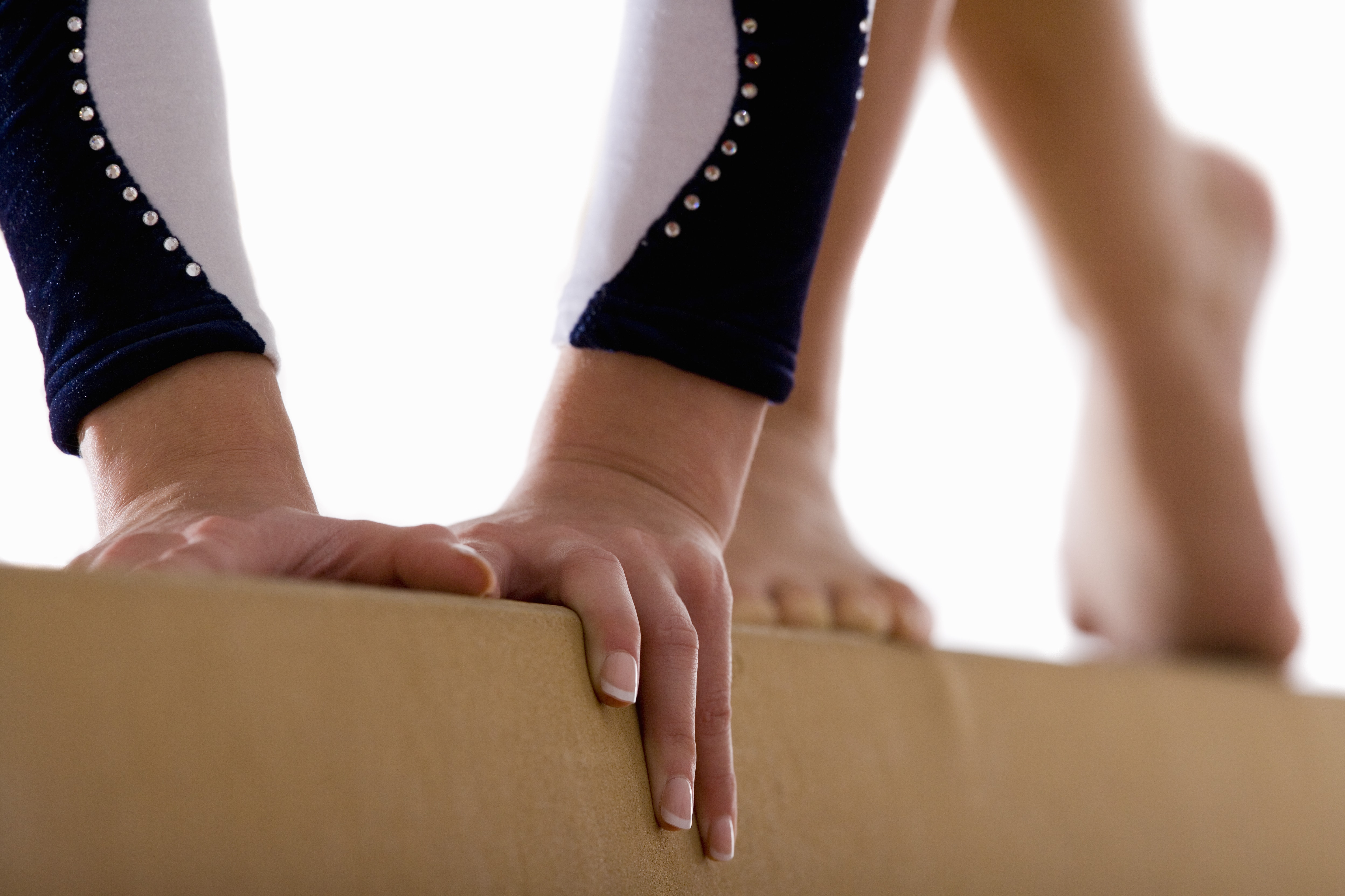 Female gymnast performing on balance beam, close-up, low section