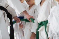 Aikido trainer tying belt for his pupil before competition
